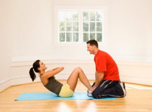 Man holding woman's feet down as she does sit-up exercises.